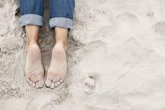 Piedi sabbiosi della giovane donna sulla spiaggia Immagine Stock
