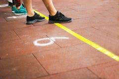 Piedi in scarpe da tennis sul pavimento Fotografie Stock Libere da Diritti