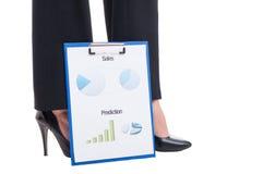 Piedi sexy della donna di affari e rapporti finanziari con i grafici Fotografia Stock