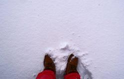 Piedi in stivali marroni coperti in neve fotografie stock libere da diritti