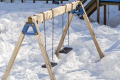 Swings seat for children under the snow Royalty Free Stock Photo