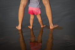 Piedini del bambino e della madre in specchio dell'acqua fotografia stock libera da diritti