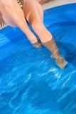 Piedini della donna in acqua blu della piscina Fotografie Stock