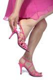 Piedini della donna che mettono sui pattini del tallone su bianco Immagini Stock