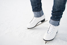 Piedini della donna nei pattini di ghiaccio bianchi Immagine Stock Libera da Diritti