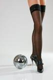 Piedini e sfera femminili lunghi della discoteca fotografie stock