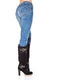 Piedini femminili in blue jeans ed alti caricamenti del sistema immagine stock libera da diritti