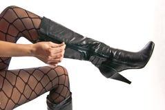 Piedini femminili in pantyhose e pattini sugli alti talloni Fotografia Stock