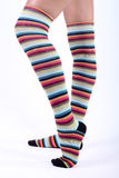 Piedini femminili in stripy sopra i calzini del ginocchio Immagini Stock