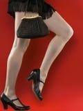 Piedini lunghi della donna sopra colore rosso. Borsa della holding Fotografia Stock Libera da Diritti