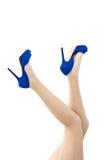 Piedini lunghi sexy in pattini blu degli alti talloni Fotografie Stock