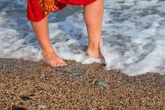 Piedini nudi della donna nell'onda del mare Immagini Stock