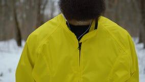 Piedistallo sparato del maschio caucasico dei pantaloni a vita bassa barbuti con gli occhi azzurri nella foresta di inverno archivi video