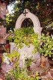 Piedra bien para el agua adornada con las flores Fotos de archivo libres de regalías