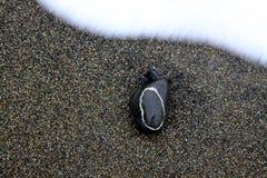 Piedra circular del modelo en una playa   fotos de archivo