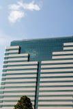 Piedra clásica y edificio de cristal azul debajo de Sunny Sky Fotos de archivo
