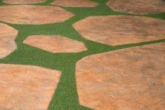 Piedra de Brown y camino artificial de la hierba del césped imagen de archivo libre de regalías