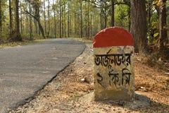 Piedra de la milla cerca del camino fotos de archivo