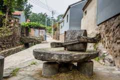 Piedra de molino grande en el campo para la producción del grano Imágenes de archivo libres de regalías