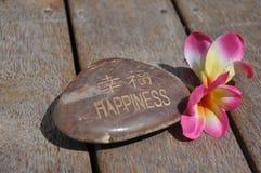Piedra del deseo de la felicidad con las flores del Frangipani Fotos de archivo