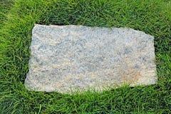 Piedra del granito con la frontera de la hierba Imagen de archivo