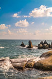 Piedra en el mar con la onda Foto de archivo libre de regalías