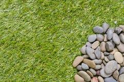 Piedra en fondo de la hierba Imagenes de archivo