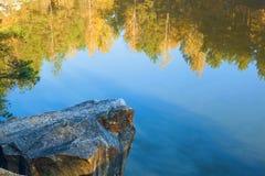 Piedra en fondo del lago y la reflexión de árboles en agua Foto de archivo