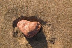 Piedra en forma de corazón en la arena de una playa Imagen de archivo