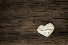 Piedra en la forma del corazón en fondo de madera natural Fotos de archivo libres de regalías