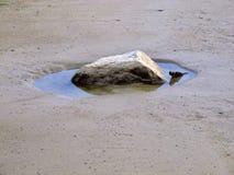 Piedra en la piscina de agua en la playa foto de archivo