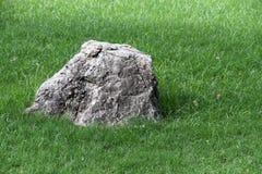 Piedra grande entre una hierba verde Símbolo Foto de archivo libre de regalías