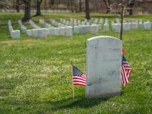 Piedra grave blanca sola con la bandera de los E.E.U.U. en el cementerio nacional de Arlington, Virginia fotografía de archivo libre de regalías