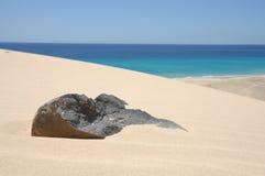 Piedra negra volcánica en la arena, Fuerteventura Foto de archivo