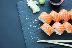 Piedra oscura clásica del rollo de Philadelphia en el tablero Salmones, queso de Philadelphia, pepino, aguacate Sushi japonés tap Fotografía de archivo libre de regalías