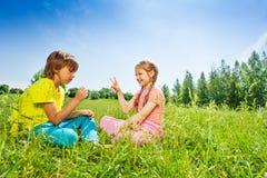 Piedra papel o tijera del juego de la muchacha y del muchacho en hierba imagen de archivo libre de regalías