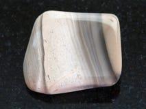 piedra pulida del pedernal en fondo oscuro imagenes de archivo