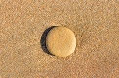 Piedra redonda en la arena mojada Fotos de archivo libres de regalías