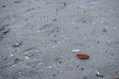 Piedra roja en la arena imagenes de archivo