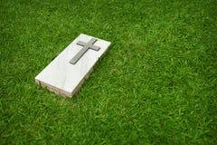 Piedra sepulcral de mármol con la cruz cristiana en un césped verde Fotos de archivo libres de regalías