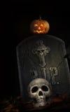 Piedra sepulcral fantasmagórica con el cráneo y la calabaza en negro Imágenes de archivo libres de regalías