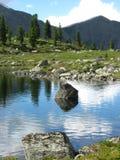 Piedra sola en el lago en el fondo de montañas y del taiga hermosos fotografía de archivo