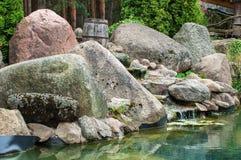 Piedra y charca naturales en jardín imagen de archivo libre de regalías