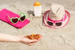 Piedras ambarinas a disposición y accesorios para las vacaciones en la arena en la playa, tiempo de verano Fotografía de archivo