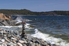 Piedras apiladas en la costa y ondas en primero plano fotos de archivo