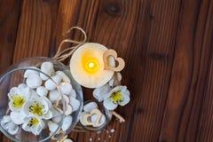 Piedras blancas en un florero de cristal, flores y una vela grande para el balneario y la relajación Fotos de archivo libres de regalías