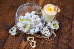 Piedras blancas en un florero de cristal, flores y una vela grande para el balneario y la relajación Fotografía de archivo libre de regalías