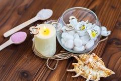 Piedras blancas en un florero de cristal, flores y una vela grande para el balneario y la relajación Imagenes de archivo