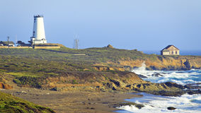 Piedras Blancas Light Station. Panoramic view of lighthouse on rugged coastline with crashing waves royalty free stock images