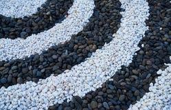 Piedras blancos y negros puestas en semi-círculo Imágenes de archivo libres de regalías